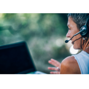 person wearing headset infront of laptop, outdoors
